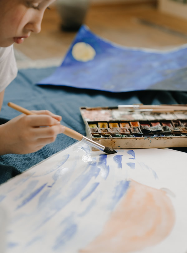 Child painting in a Montessori Nursery learning environment