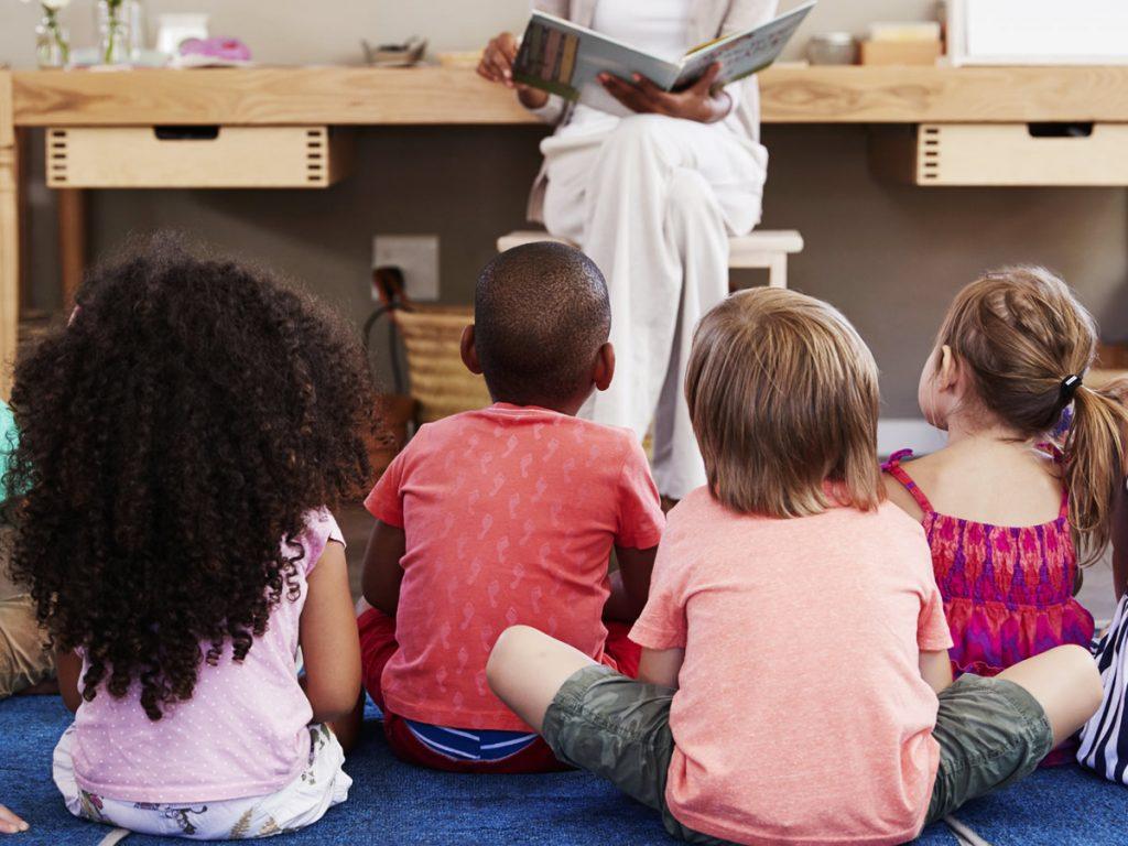 children in class teacher reading story